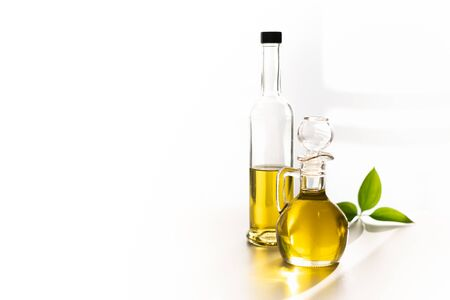 against the window, olive oil in a decanter and in a glass bottle, with a green leaf Zdjęcie Seryjne