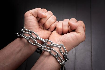 male hands on a gray background wrapped in a metal chain. prison concept Standard-Bild