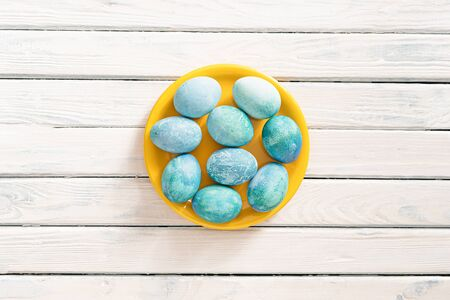 blue marble eggs lie on a white background in a yellow plate, as a symbol of Easter