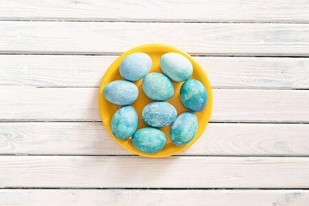 blaue Marmoreier liegen auf einem weißen Hintergrund in einem gelben Teller, als Symbol für Ostern