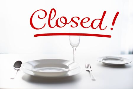 table setting in a restaurant. The word Closed - as a concept for closing restaurants