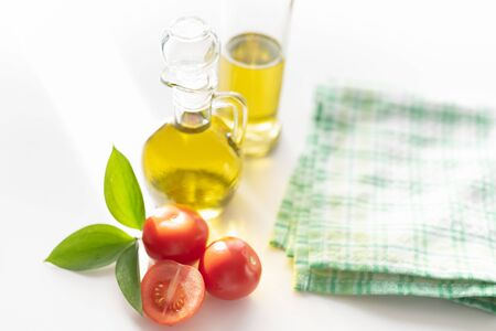 on a white background vegetable olive oil in a glass decanter. Nearby are slices of tomatoes and a green leaf.