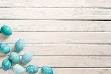 on a white background in a yellow plate are blue marble eggs lie as an Easter symbol