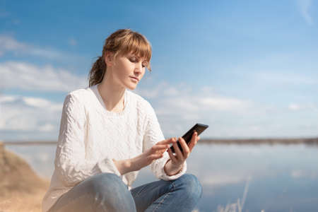 woman with red hair dressed in a white sweater sitting on the nature with a phone. Remote work concept
