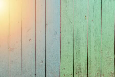 background for text - vertical wooden boards of blue and green color with a glare from the sun Imagens