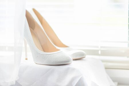 white shoes for the bride on a background of a bright window with jalousie