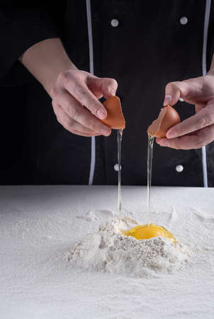 The process of making dough. female chef breaks a chicken egg into wheat flour.