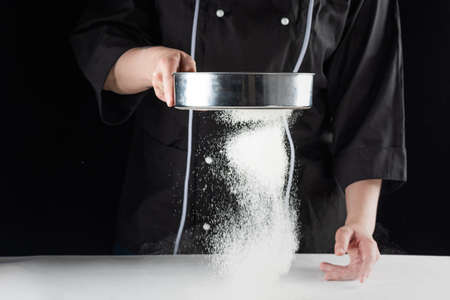 a dark background bakers hands sift white wheat flour over a sieve over