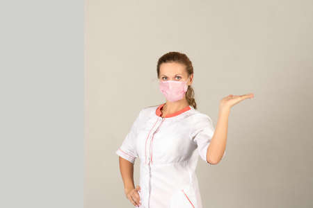 A woman in a protective medical mask and white coat points to a place for text.