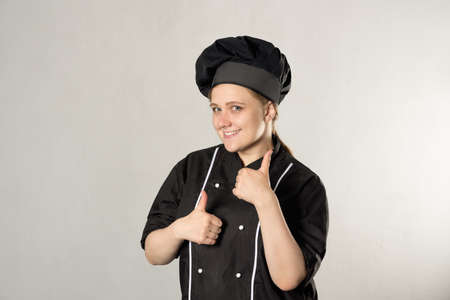 like - gesture with hands, shows a female chef in a black uniform on a gray background and smiling 免版税图像