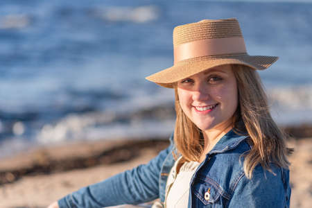 The concept of peace of mind and happiness. A woman with blond hair in a straw hat and a denim jacket stands on the background of the sea and enjoys the sun.