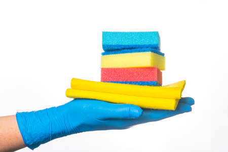 a hand in a blue glove holds multi-colored sponges and a yellow rag for cleaning rooms. on a white background. 免版税图像
