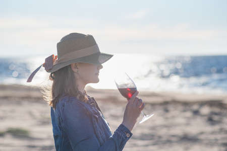 woman in a straw hat stands by the sea with a glass of wine, rear view 免版税图像