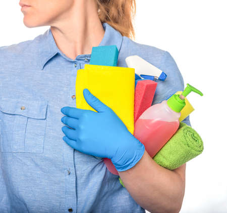 Woman in blue uniform and gloves holds liquid cleaning products and sponges. 免版税图像