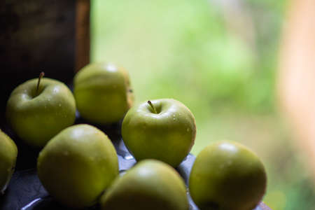 Green apples in drops of water on a black metal board on a background of green grass