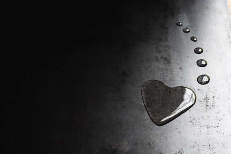 on a gray sheet of iron lies a drop of water in the shape of a heart