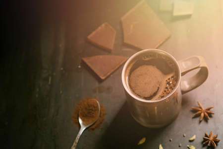 metal thermo mug with coffee on a gray background with pieces of chocolate, a spoon with ground coffee and star anise 免版税图像