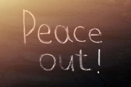 lettering made in chalk on a metal board - peace out