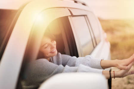 young woman smiling with closed eyes, sticking her hands out of the car window. The shining of the sun in the window. 免版税图像