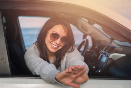 Happy young brunette smiling from the window of a white car on a background of blue sea.