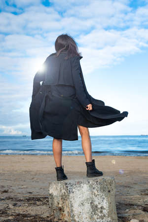 young woman in a black cloak developing in the wind and boots, stands on a stone by the sea.