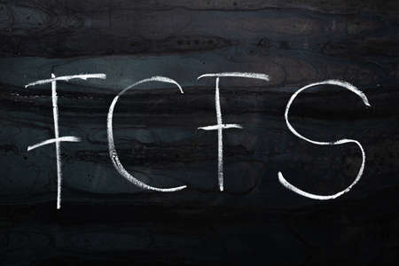 the word FCFS - first come, first served - is written in chalk on a black plate. 免版税图像