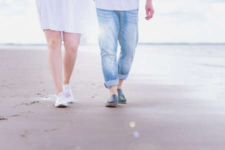 male and female legs in sports shoes walk along the beach against the background of the sea.