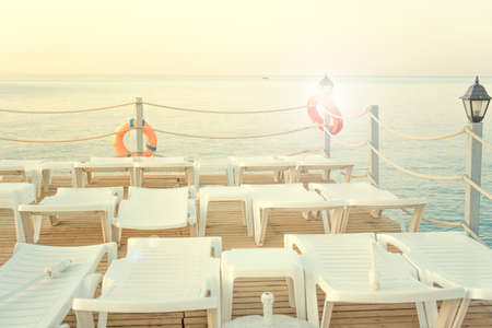 white sun loungers on the background of the sea, stand on the pier at dawn. orange lifebuoys. 免版税图像