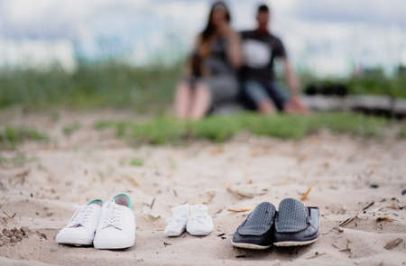 Three pairs of shoes on the sand - adult and child for newborns.