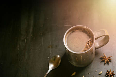 metal thermo mug with coffee on a gray background with star anise and cardamom