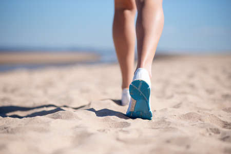 sports female legs in sneakers on the beach against the background of the blue sea. The sportswoman runs on the sand.