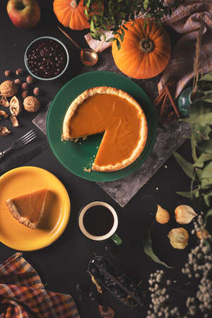 Orange pumpkin pie with a pumpkin, mulled wine, nuts and blackthorn on wooden table