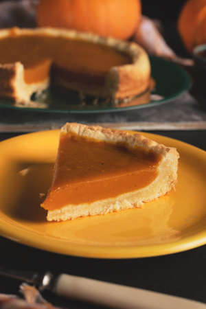 Orange pumpkin pie for Thanksgiving. a slice of pumpkin pie on a yellow plate close-up on a dark background. 免版税图像