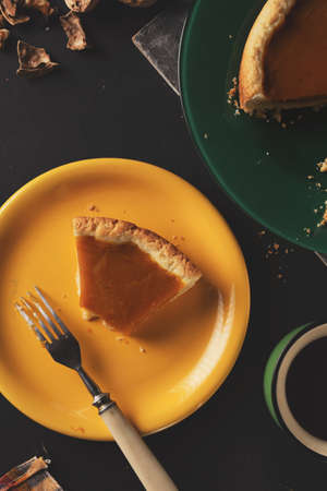 On a plate, crumbs and a fork on a dark background. a slice of pumpkin pie on a yellow plate while eating. 免版税图像