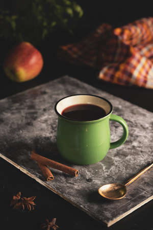 in a green mug on a black background hot mulled wine from red wine with the addition of apple and cinnamon. 免版税图像