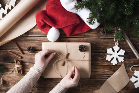 DIY Christmas gifts and packaging of kraft paper on a wooden table. The process of making gifts in a rustic style for the New Year. 免版税图像