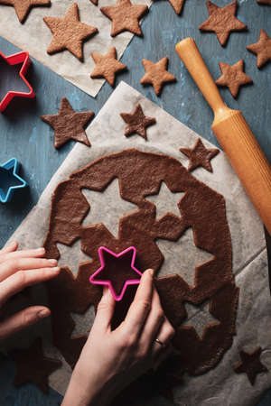 The process of making gingerbread for Christmas, in the form of stars on a blue background