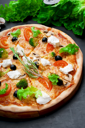 Pizza is cut with champignons, tomatoes, feta,cheese, broccoli, olives on background of lettuce. photo