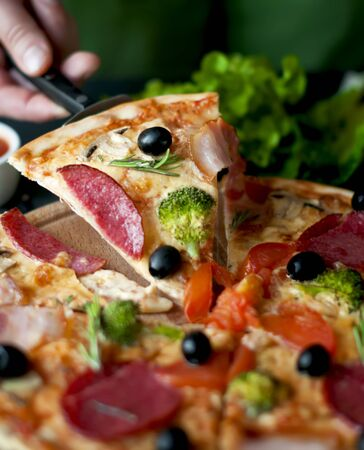 A slice of pizza in his hand on the blade with salami, broccoli, tomato, olives photo