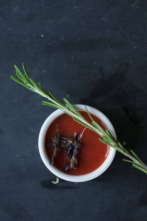 flavorings: tomato sauce with basil and rosemary on dark background. Stock Photo