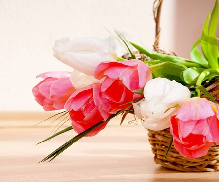 Bouquet of spring tulips in a wicker basket - space for text. photo