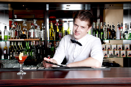 Young smiling bartender taking an order. photo