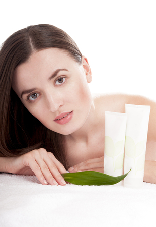 humidify: Woman with well-groomed skin near organic cosmetics - isolated on white background. Skin care concept.