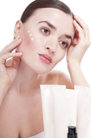 humidify: Sensual woman applying cosmetic cream treatment on her face. Skin care concept.
