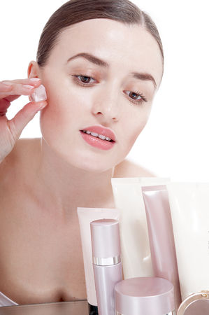 humidify: Beautiful woman applying  ice cube treatment on face. Skin care concept.