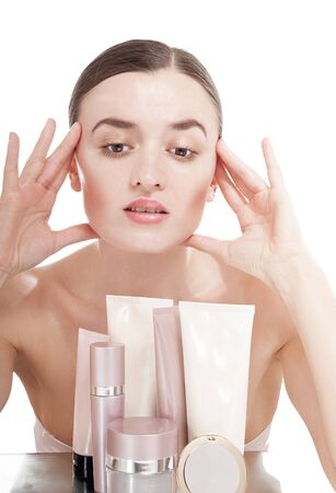 humidify: Young woman with  a well-groomed skin near the creams cosmetics. Skin care concept.