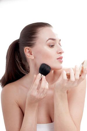 primp: Bella giovane donna preens con un pennello per blush, guardarsi allo specchio. Isolato su sfondo bianco.