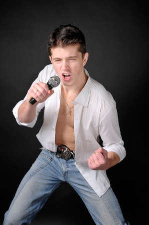 spunky: Expressively man singing with microphone on dark background. Stock Photo