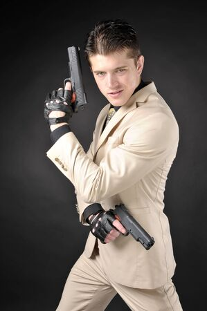 malefactor: Handsome man with a gun wearing a white suit Stock Photo