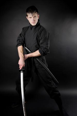 saboteur: Ninja - spy, saboteur, stealth assassin of feudal Japan. Ninja with sword over dark background.